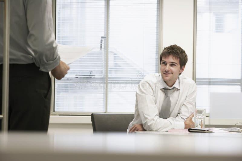 Hombres de negocios sonrientes que escuchan el colega masculino fotografía de archivo