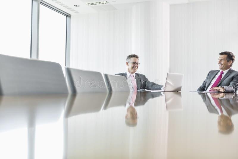 Hombres de negocios sonrientes que hablan en la sala de conferencias foto de archivo libre de regalías