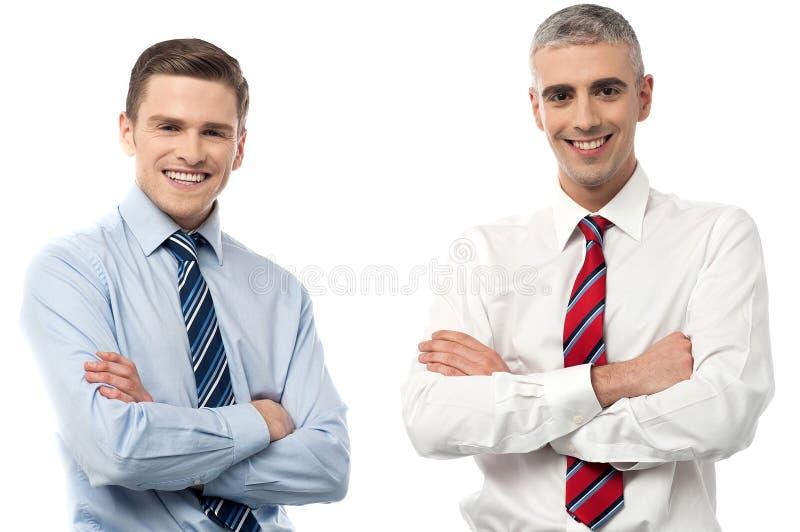 Hombres de negocios sonrientes que presentan junto imagenes de archivo