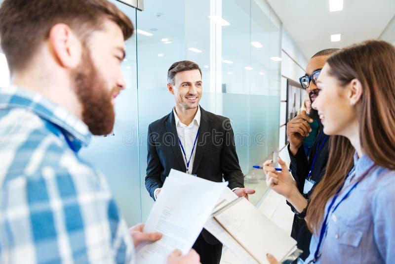 Hombres de negocios sonrientes que se colocan y que hablan con el líder de equipo foto de archivo