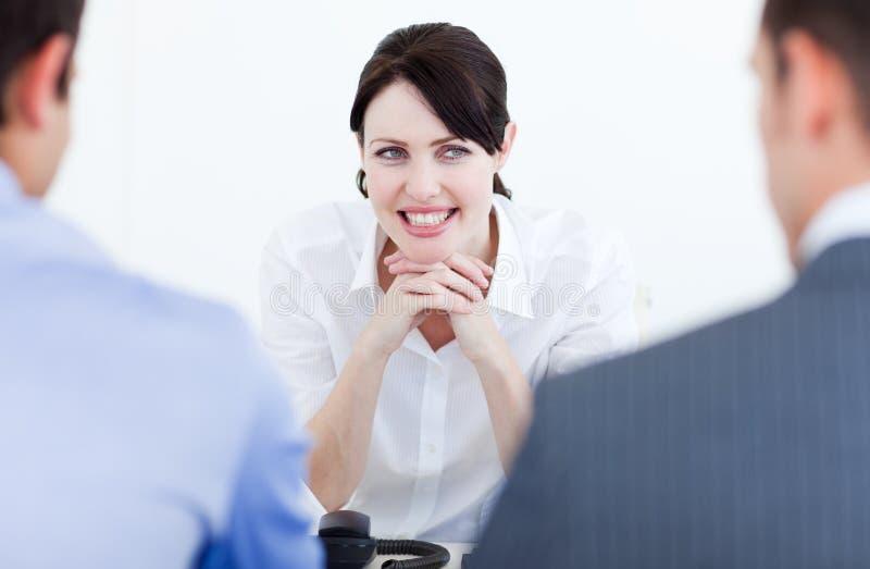 Hombres de negocios sonrientes que tienen una entrevista de trabajo foto de archivo libre de regalías