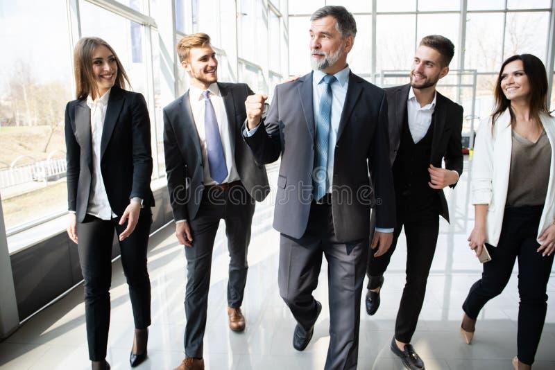 Hombres de negocios de Team Walking In Modern Office, hombres de negocios confiados y empresarias con el líder maduro In Foregrou fotos de archivo