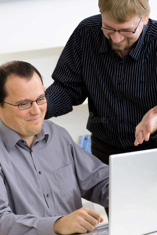 Hombres de negocios usando el ordenador portátil foto de archivo