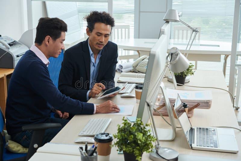 Hombres de negocios usando la tableta en oficina imagen de archivo