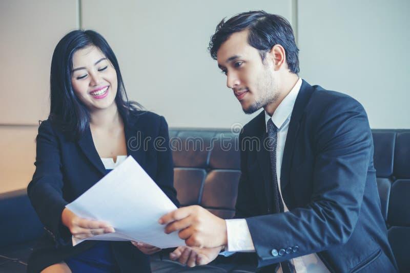 Hombres de negocios y empresarias que discuten documentos e ideas adentro fotografía de archivo libre de regalías