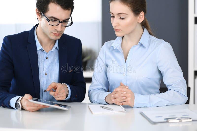 Hombres de negocios y mujer que usa la tableta en oficina moderna Colegas o encargados de compa??a en el lugar de trabajo socios fotos de archivo