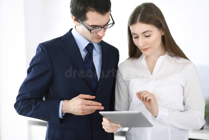 Hombres de negocios y mujer que usa la tableta en oficina moderna Colegas o encargados de compa??a en el lugar de trabajo socios foto de archivo libre de regalías
