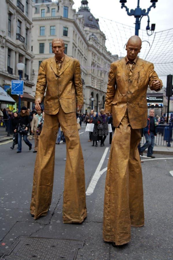 Hombres de oro en los zancos fotos de archivo