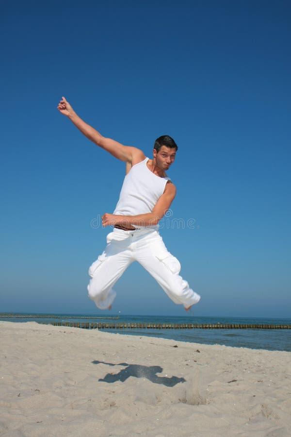 Hombres de salto vestidos blancos en el mar foto de archivo libre de regalías