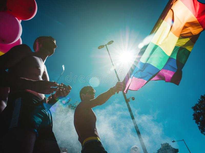 Hombres del orgullo gay que bailan a gente de LGBT en el camión con la bandera del arco iris imagen de archivo libre de regalías