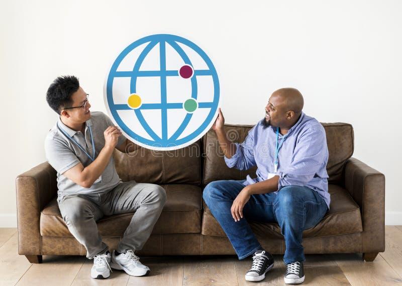 Hombres diversos con el icono de Internet en el sofá imágenes de archivo libres de regalías