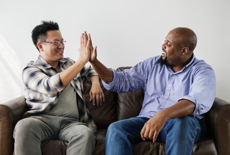 Hombres diversos que se unen a las manos juntas imagen de archivo