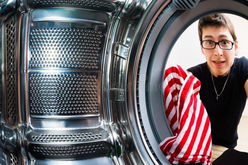 Hombres divertidos que cargan la ropa a la lavadora imagen de archivo