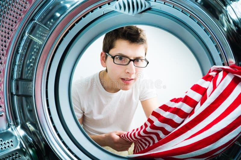 Hombres divertidos que cargan la ropa a la lavadora foto de archivo
