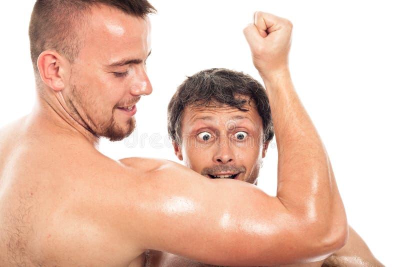 Hombres divertidos que miran bíceps imágenes de archivo libres de regalías