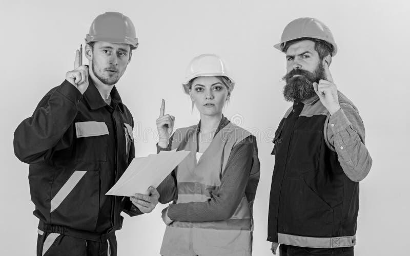 Hombres en cascos, uniforme y mujer Constructor e ingeniero imagen de archivo libre de regalías