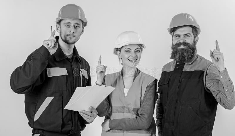 Hombres en cascos, uniforme y mujer Idea y creatividad foto de archivo