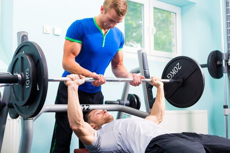 Hombres en el entrenamiento del gimnasio del deporte con el barbell foto de archivo libre de regalías