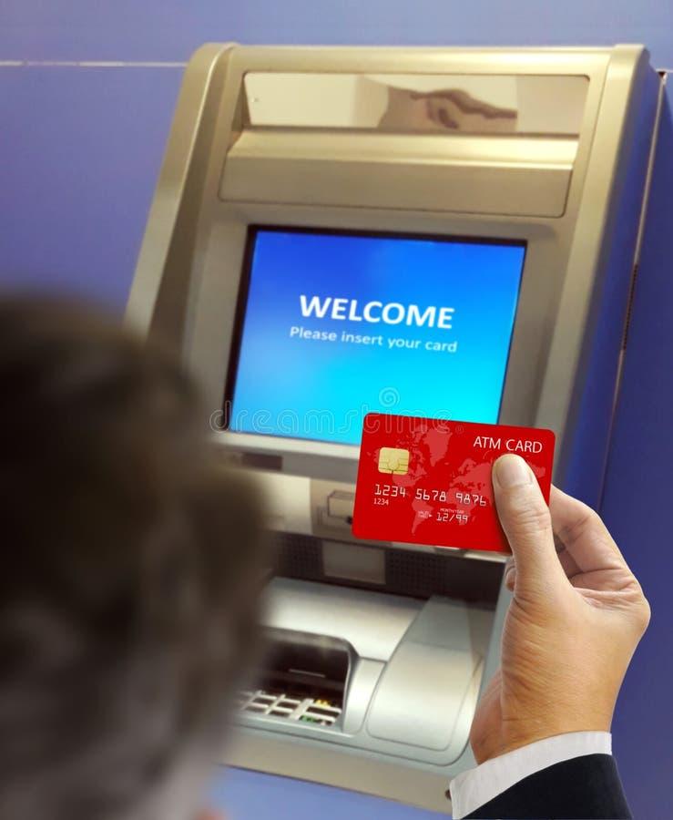 Hombres en la máquina de la atmósfera que hace la transacción de actividades bancarias imágenes de archivo libres de regalías