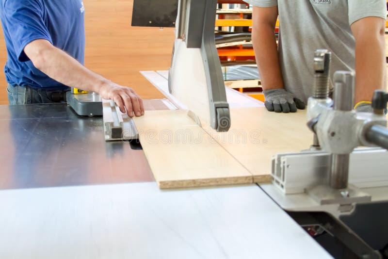 Hombres en la madera del sawing del trabajo Circular vio Una máquina que asierra la madera, el tablero de partícula y el panel de fotografía de archivo