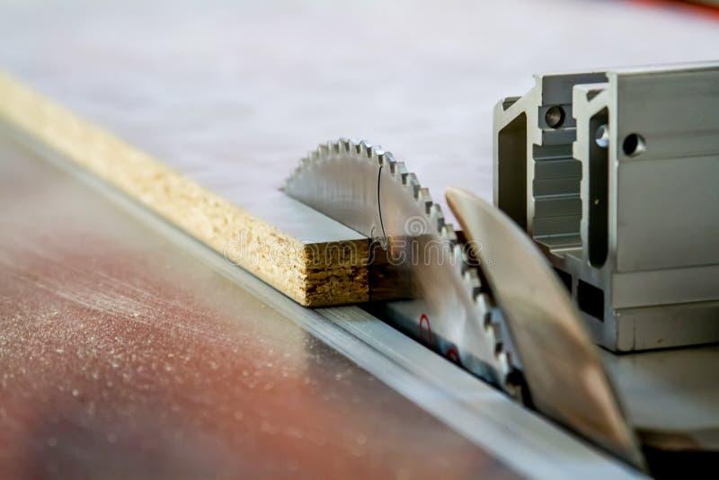 Hombres en la madera del sawing del trabajo Circular vio Una máquina que asierra la madera, el tablero de partícula y el panel de fotos de archivo libres de regalías