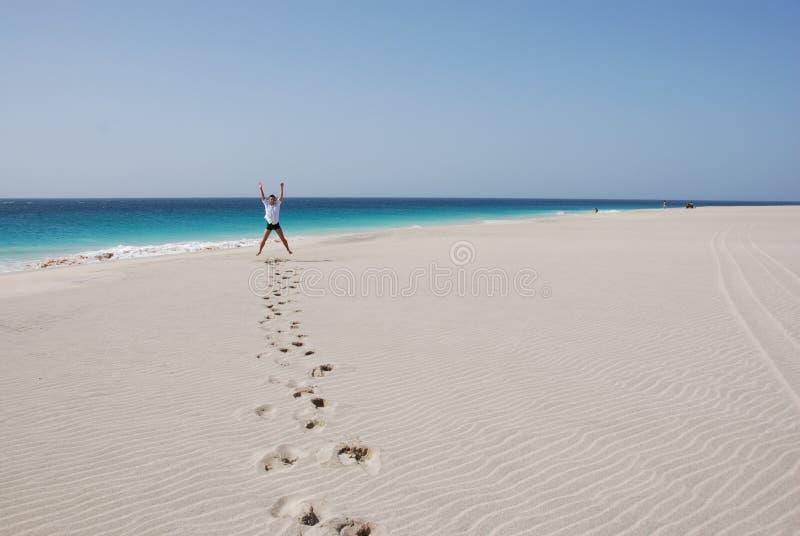 Hombres en la playa arenosa - océano y cielo azules imágenes de archivo libres de regalías