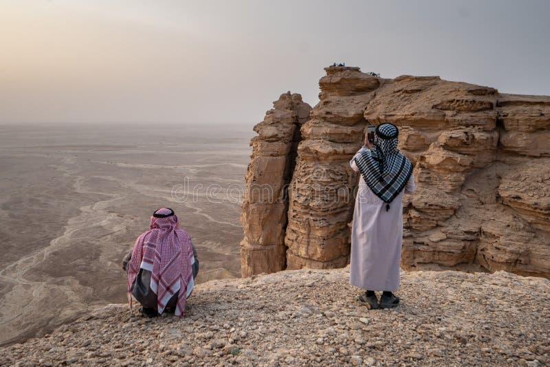 2 hombres en ropa tradicional en el borde del mundo cerca de Riad en la Arabia Saudita fotos de archivo