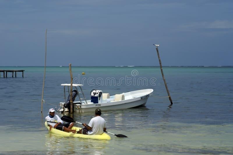 Hombres en un kajak por un barco imagenes de archivo
