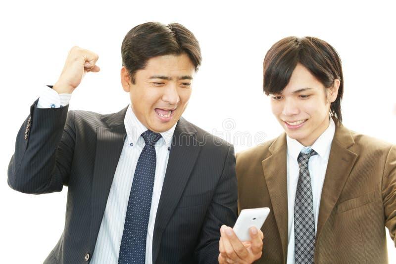 Hombres felices con el teléfono elegante fotografía de archivo libre de regalías