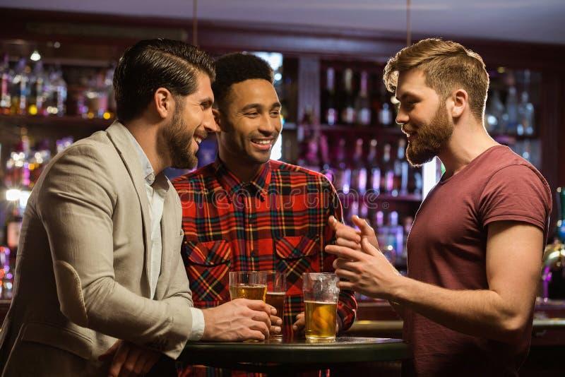 Hombres felices jovenes que beben la cerveza y que hablan en café imagen de archivo libre de regalías