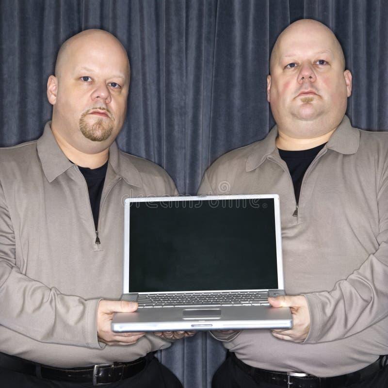 Hombres gemelos con la computadora portátil imagen de archivo libre de regalías
