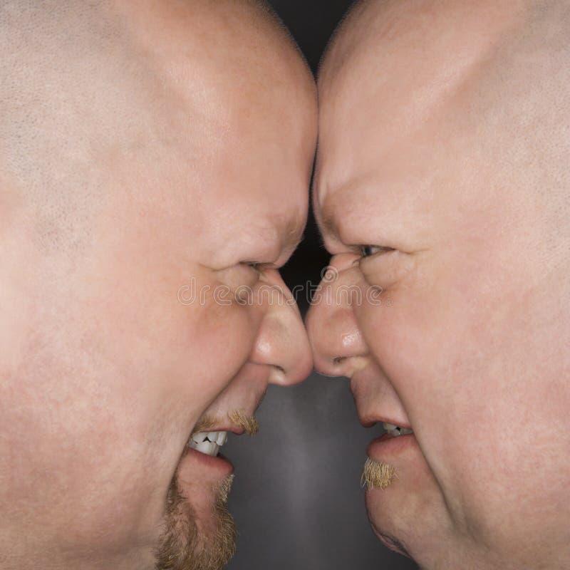 Hombres gemelos que hacen frente apagado. imagen de archivo