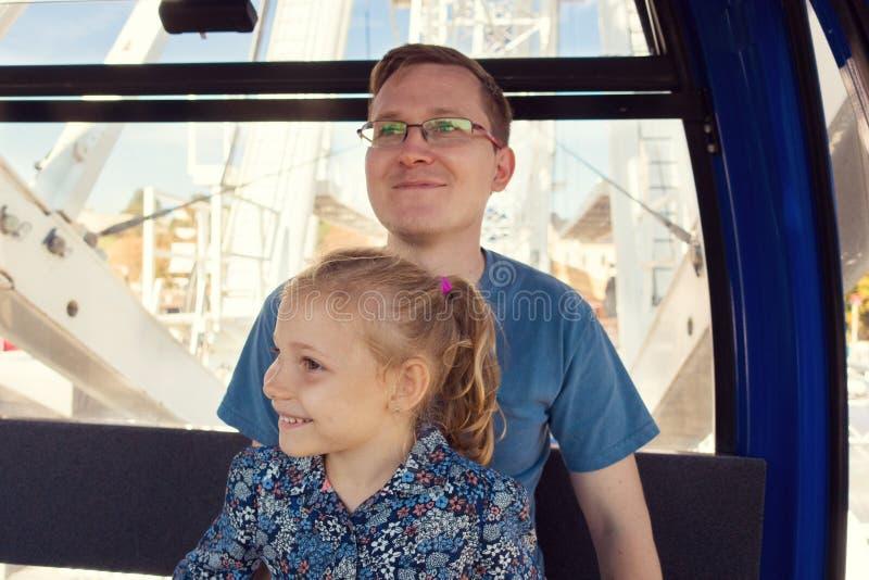 Hombres hermosos con su hija bastante feliz que se sienta en los ferris w foto de archivo