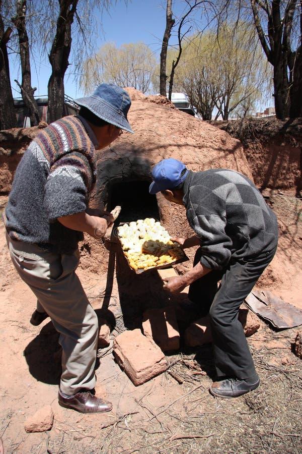 Hombres indios que cocinan en Clay Oven en Bolivia imagenes de archivo