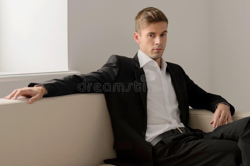Hombres jovenes confiados. Hombres jovenes hermosos en el formalwear que se sienta encendido fotografía de archivo