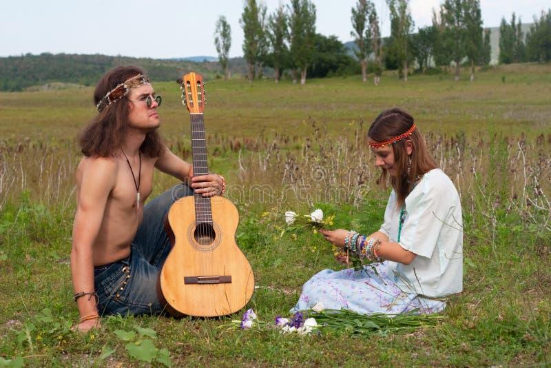 Hombres jovenes del hippie con la guitarra y la mujer fotos de archivo libres de regalías