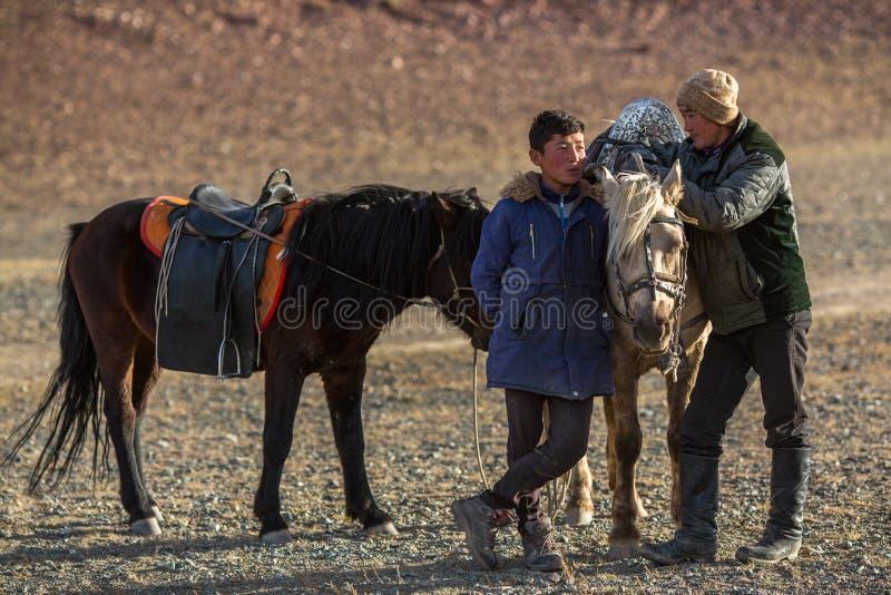 Hombres jovenes Eagle Hunters que se coloca cerca de sus caballos durante la caza en el desierto de la montaña de Mongolia occide fotos de archivo