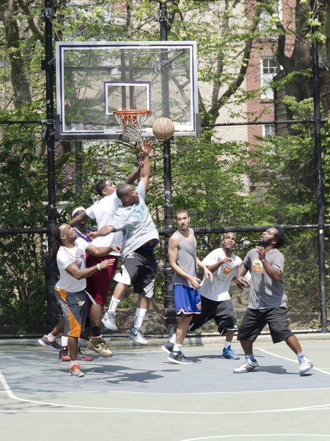Hombres jovenes en la acción que juega a baloncesto en la calle imagen de archivo libre de regalías