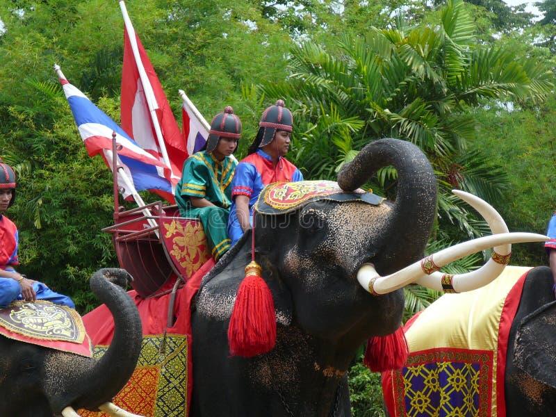 Hombres jovenes en los trajes antiguos tailandeses que montan un elefante imágenes de archivo libres de regalías