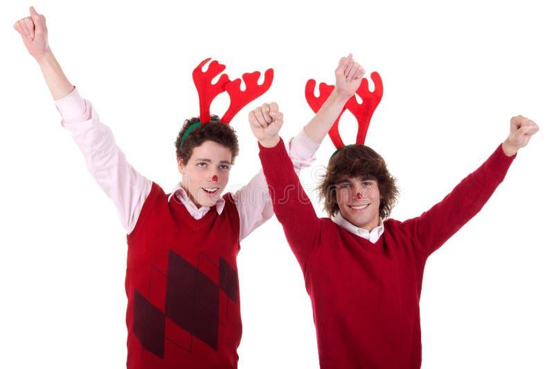 Hombres jovenes felices que desgastan los claxones del reno, con los brazos foto de archivo libre de regalías