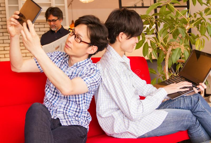 Hombres jovenes japoneses que usan la PC del ordenador portátil y el dispositivo de la tableta para mirar contenido en Internet fotos de archivo