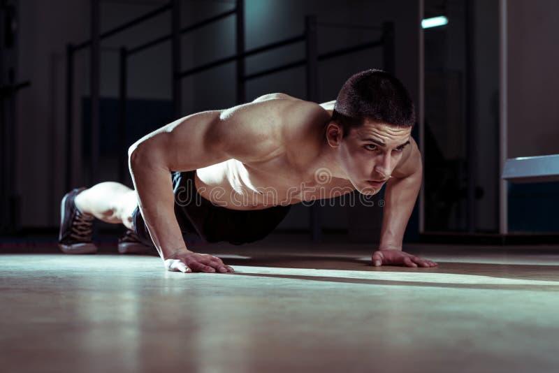 Hombres jovenes que hacen flexiones de brazos imagenes de archivo