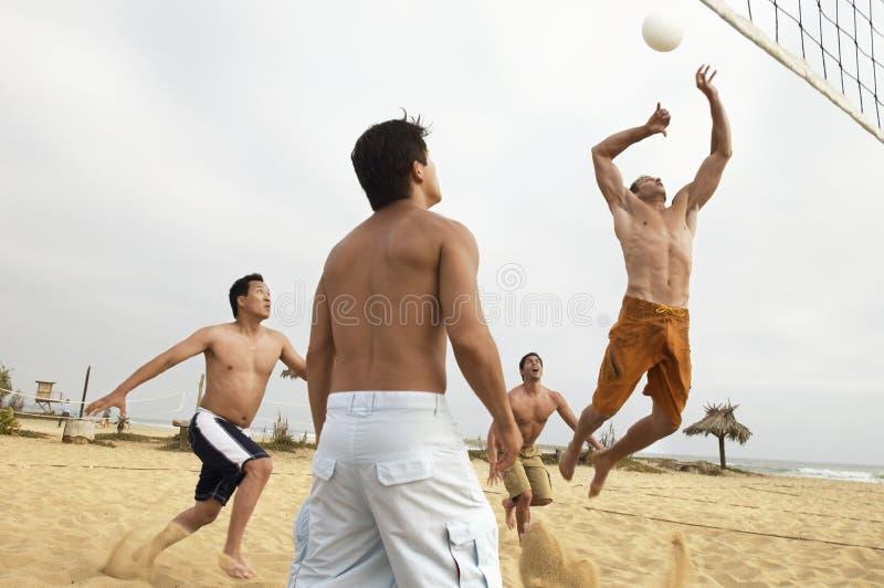 Hombres jovenes que juegan a voleibol en la playa imagen de archivo