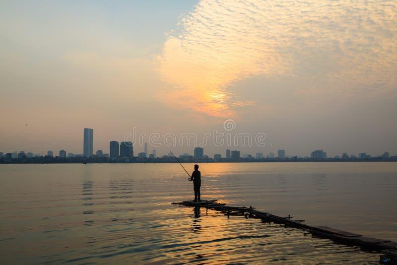 Hombres jovenes que pescan en el lago del oeste (Ho tay) imagen de archivo libre de regalías