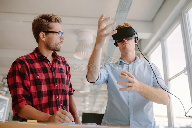 Hombres jovenes que prueban gafas de la realidad virtual foto de archivo