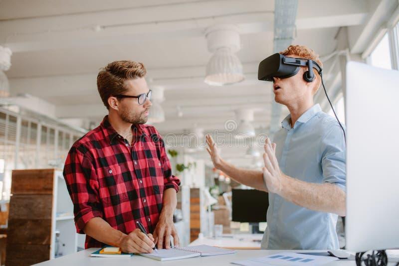 Hombres jovenes que prueban las auriculares de la realidad virtual foto de archivo libre de regalías