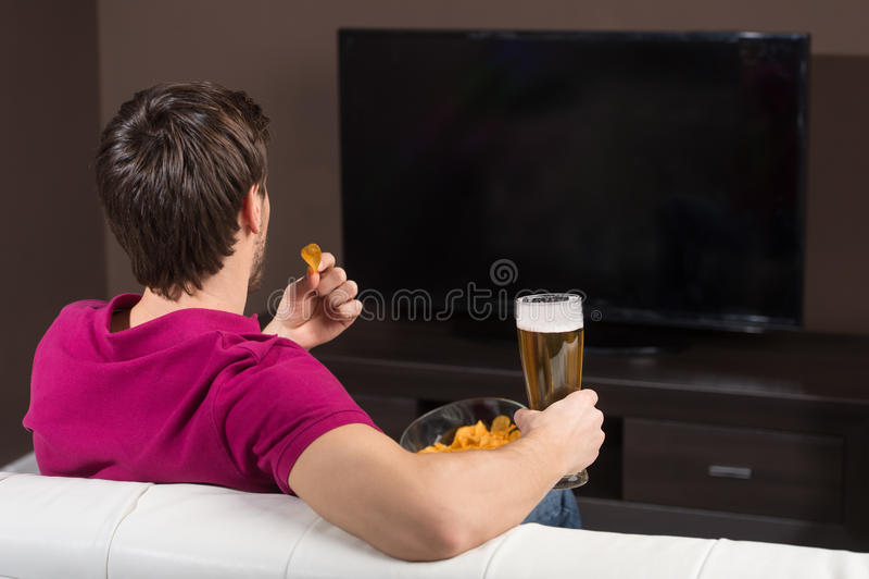 Hombres jovenes que ven la TV. Vista posterior de los hombres jovenes que beben la cerveza y fotografía de archivo libre de regalías