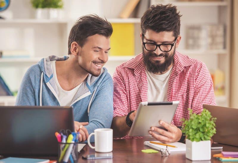 Hombres jovenes sonrientes que trabajan con el ordenador portátil y la tableta fotos de archivo libres de regalías
