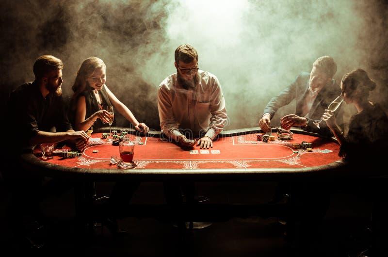 Hombres jovenes y mujeres que juegan el póker en la tabla en humo imagen de archivo