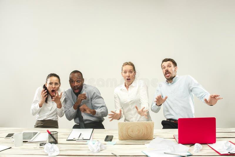 Hombres jovenes y mujeres que se sientan en la oficina y que trabajan en los ordenadores portátiles Concepto de las emociones imagen de archivo